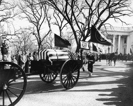 "John F. Kennedy's funeral procession leaves the White House on the way to St. Matthew's Cathedral on Nov. 25, 1963. A color guard holding the presidential colors, and the riderless horse, ""Black Jack,"" follow behind. Photo by Abbie Rowe"