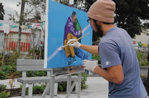 During St. Mary's vigil for homeless people who died in the past year, Dave Kim, an artist with the Community Rejuvenation Project, painted a portrait of a homeless man holding and comforting another person on the streets. Mina Gaskell Photo