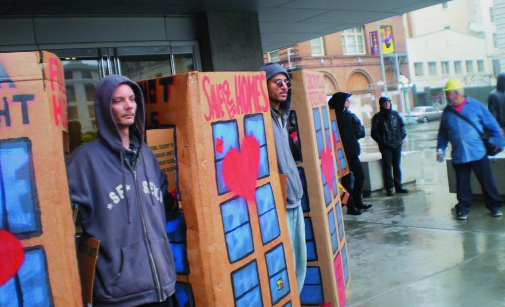 """SAVE OUR HOMES.""   Protesters made cardboard replicas of homes to dramatize the need for housing. Carol Harvey photo"