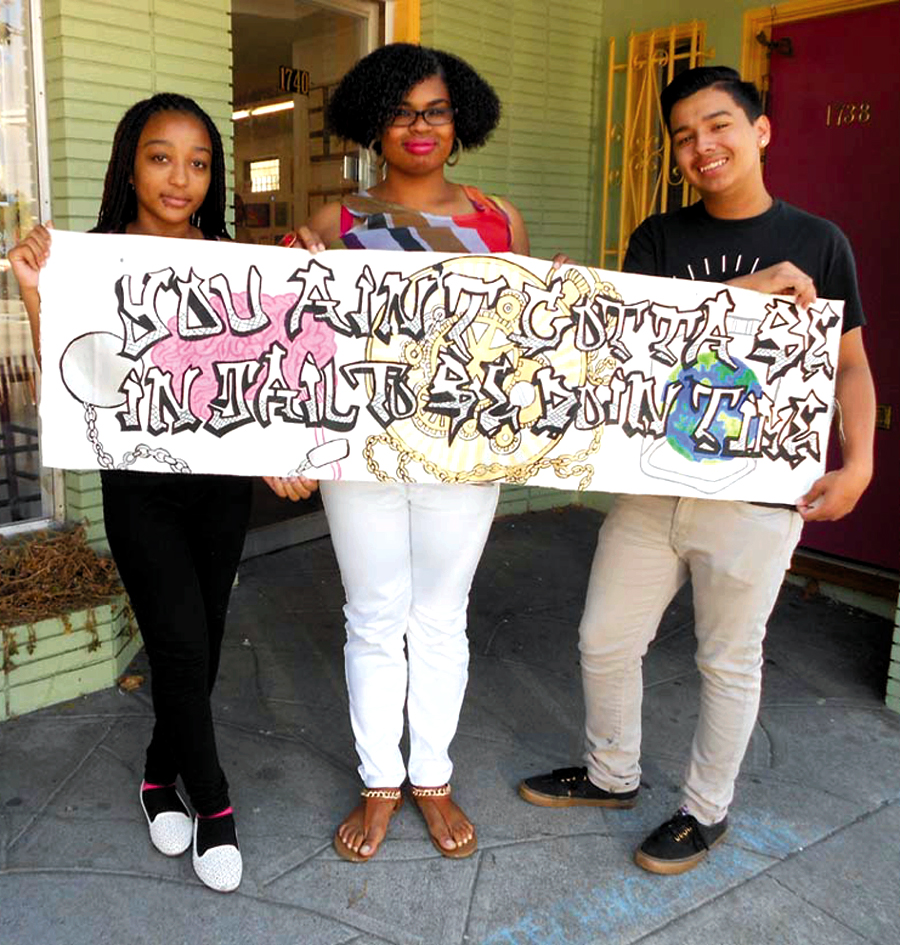 "Young artists Alasia Ayler, Brianna Pierce and Vernon Neely display their artistic statement: ""You ain't gotta be in jail to be doing time."" Lydia Gans photo"