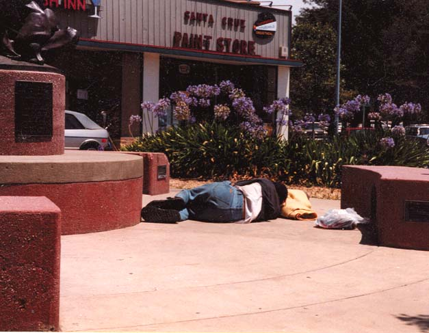 A homeless man sleeps on the sidewalk in Santa Cruz. Almost no thought is being given to all those left without shelter.