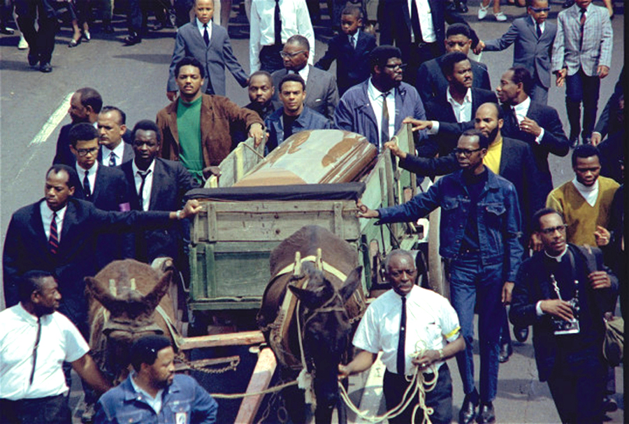Two plow mules draw the farm wagon bearing the casket of Rev. Martin Luther King, Jr. along the funeral procession route in Atlanta, Georgia, April 9, 1968.