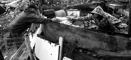 A contractor in charge of cleanup (at left) hands a warning notice to a resident of the Jungle, the nation's largest homeless encampment. Hundreds of people were warned that they would be arrested for trespassing. Photo credit: Associated Press