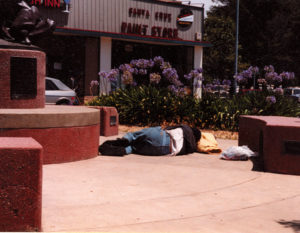 "A homeless man sleeps on the sidewalk in Santa Cruz. Homeless advocates are proposing a ""Camp of Last Resort"" to provide a safe sleeping place for thousands of people who are unsheltered and forced to sleep outdoors in a city where it is illegal to do so."