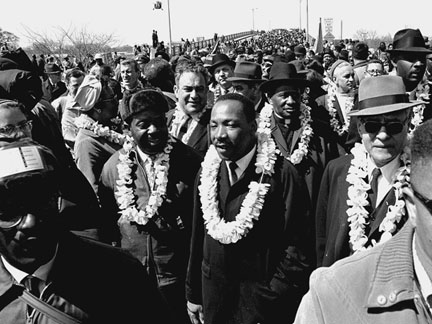 This March 21, 1965, AP photo shows Martin Luther King, Jr. and civil-rights marchers crossing the Edmund Pettus Bridge in Selma, Alabama, heading for the capitol in Montgomery. (Photo credit: AP file)