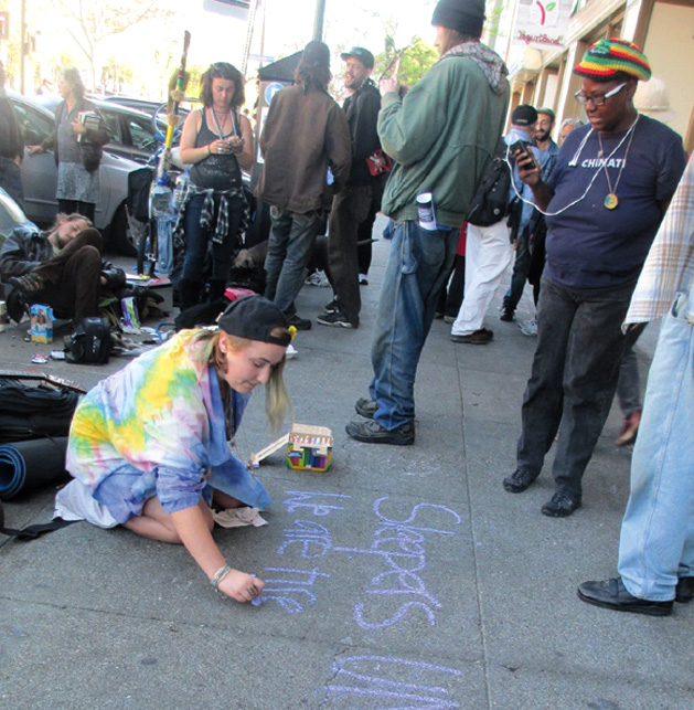 In defiance of Berkeley's laws that criminalize homeless people for sleeping outdoors, a protester uses colored chalk to speak out against repression. Sarah Menefee photo