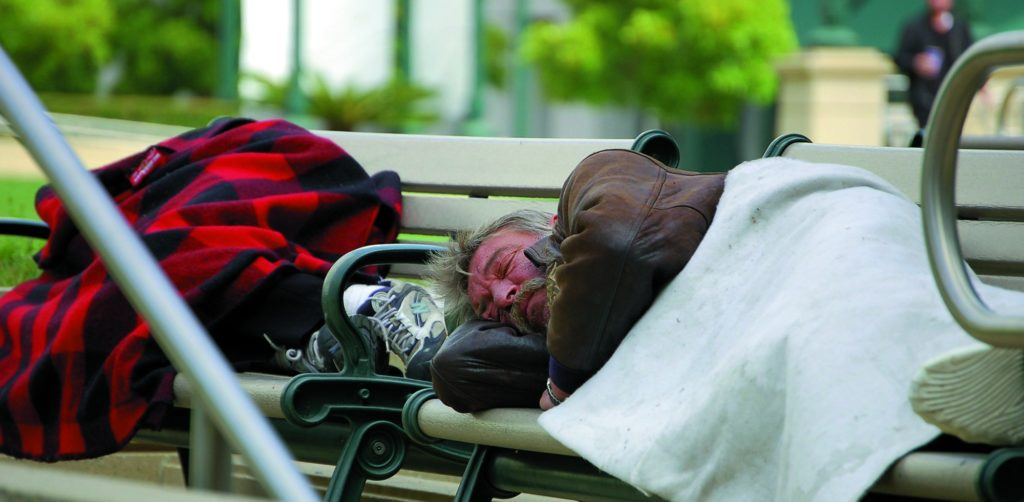 An elderly homeless man sleeps on a park bench outside Oakland City Hall.  At a time when millions of Americans are unable to afford housing, and are forced to sleep outdoors, HUD's plan to sell off the nation's public housing stock is drawing widespread opposition. Tom Lowe photo