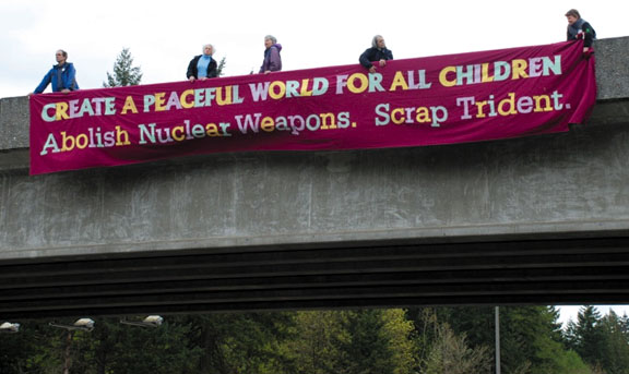 "Trident protesters on a freeway overpass: ""Create A Peaceful World For All Children. Abolish Nuclear Weapons. Scrap Trident."" Photo courtesy Ground Zero Center"