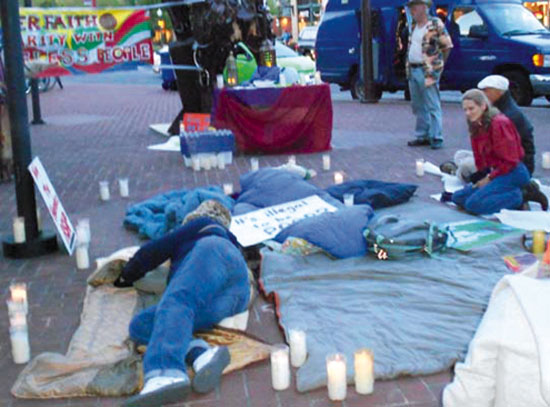 Demonstrators spread out blankets and sleeping bags and hold a nighttime vigil in downtown Berkeley to protest the criminalization of homelessness and sleeping by the Berkeley City Council.. Lydia Gans photo