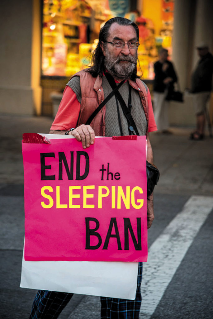"A Santa Cruz protester calls for the city government to ""End the Sleeping Ban."" Photo by Alex Darocy, Indybay.org."