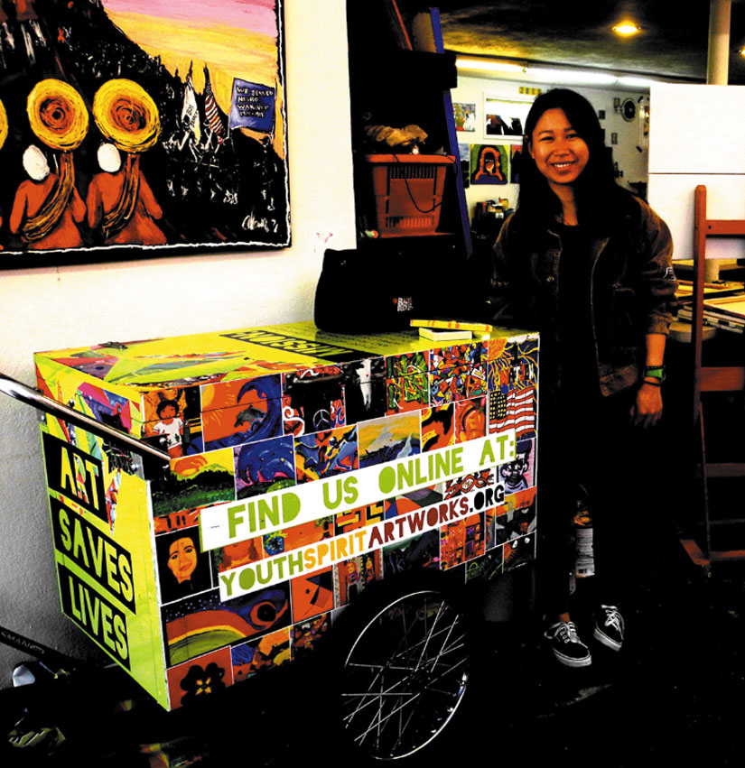"Lia Li displays an ""art cart"" used by young artists working at Youth Spirit Artworks.  Carol Denney photo"