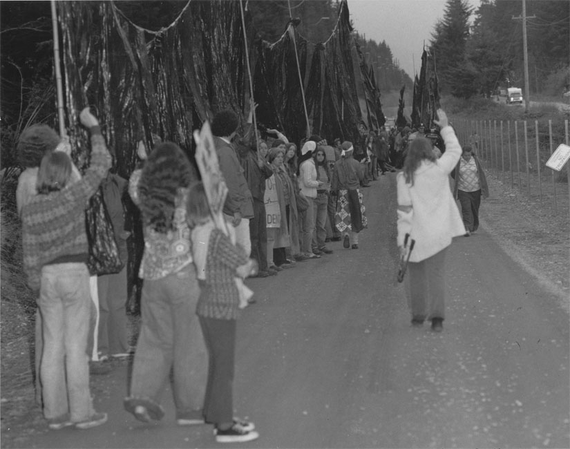"After cutting through the fence at the Trident naval base, peace activists take the ""Trident Monster"" inside the base.  Shelley Douglass is on the right, walking away from the camera, holding the bolt cutters.  Several children helped carry the monster over the fence."