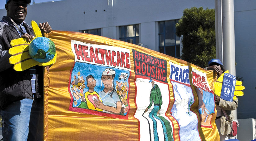 A banner carried by Oakland activists calls for health care, affordable housing, peace and food for all.
