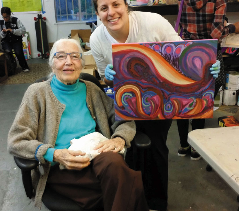 Frances Townes and Cynthia Arteaga with a painting created at Youth Spirit Artworks, a program for low-income and homeless youth.