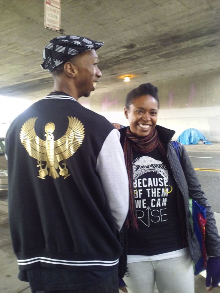 "Kwalin Kamaathi (at left) and Delene offered food and friendship to people living in Oakland homeless encampments. Delene's shirt has an abstract image of Maya Angelou. It says, ""Because of them we can rise."" Wanda Sabir photo"