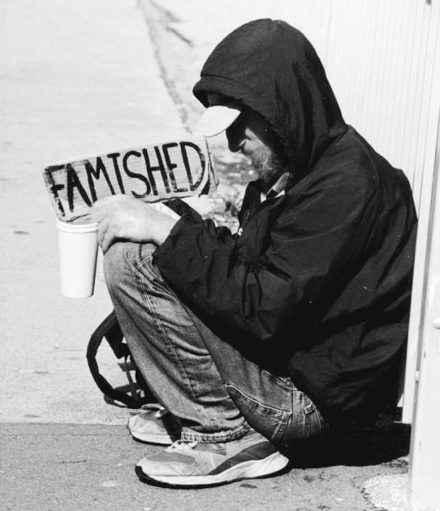 "A homeless man in San Francisco, hungry and alone on the winter streets, holds up a sign bearing a single poignant word: ""Famished."" Robert L. Terrell Photo"
