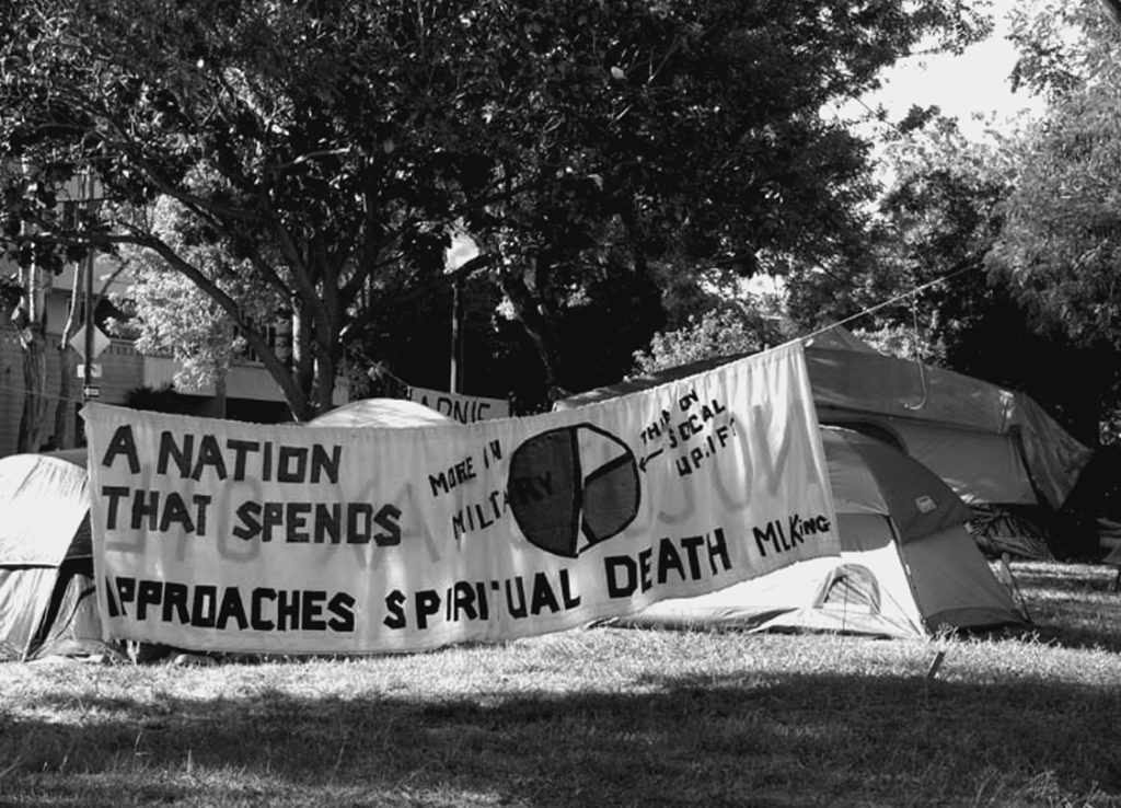 A banner at the entrance to the Arnieville encampment quotes the prophetic warning of Martin Luther King: A nation that spends more money on the military than on programs of social uplift approaches spiritual death. Photo by Lydia Gans