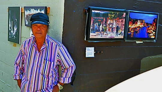 The homeless artist proudly displays his paintings at a streetside art gallery he created himself. Robert L. Terrell photo
