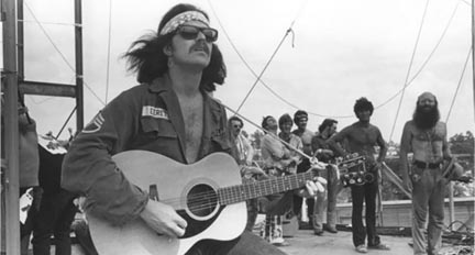 "Country Joe McDonald plays for 300,000 people at Woodstock. He said, ""They found a guitar, a Yamaha FG 150, and tied a rope on it (see the photo) and pushed me on stage. The rest is history."" Photo credit: Jim Marshall"