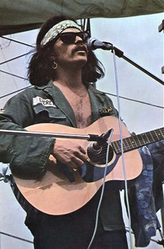 "Country Joe McDonald sings ""Fixin' to Die"" at Woodstock. Benno Friedman photo"