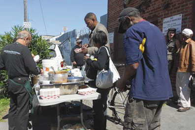 Every Thursday, Joe Liesner and Food Not Bombs volunteers serve a warm meal to the recyclers. Lydia Gans photo