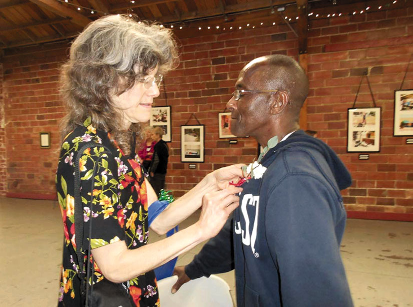 Susan Werner pins a boutonniere on Keith Arivnwine to honor his work as a photographer in documenting the conditions facing homeless people. Lydia Gans photo