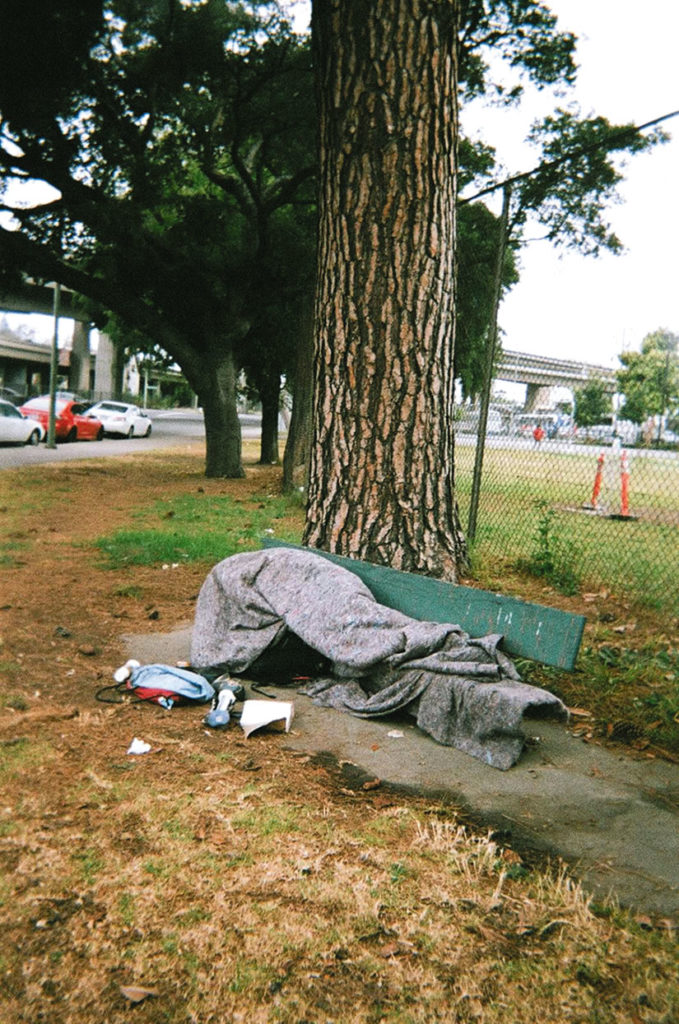 """Urban Camping."" A homeless person in Oakland makes a home from a bench and a blanket. Many survive by becoming very resourceful. Pedro Del Norte photo"