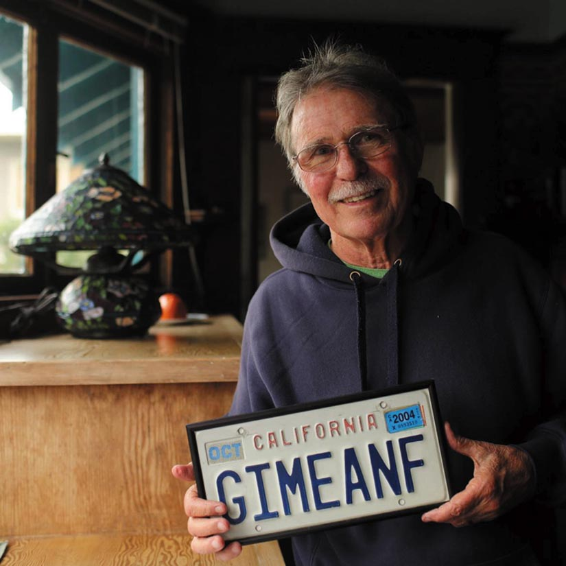 "Country Joe McDonald smilingly displays his ""Give Me an F"" license plate."