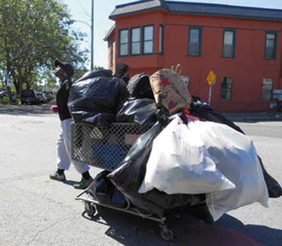 A recycler in Oakland hauls a heavily loaded shopping cart. Women recyclers are very vulnerable on the street. Lydia Gans photo