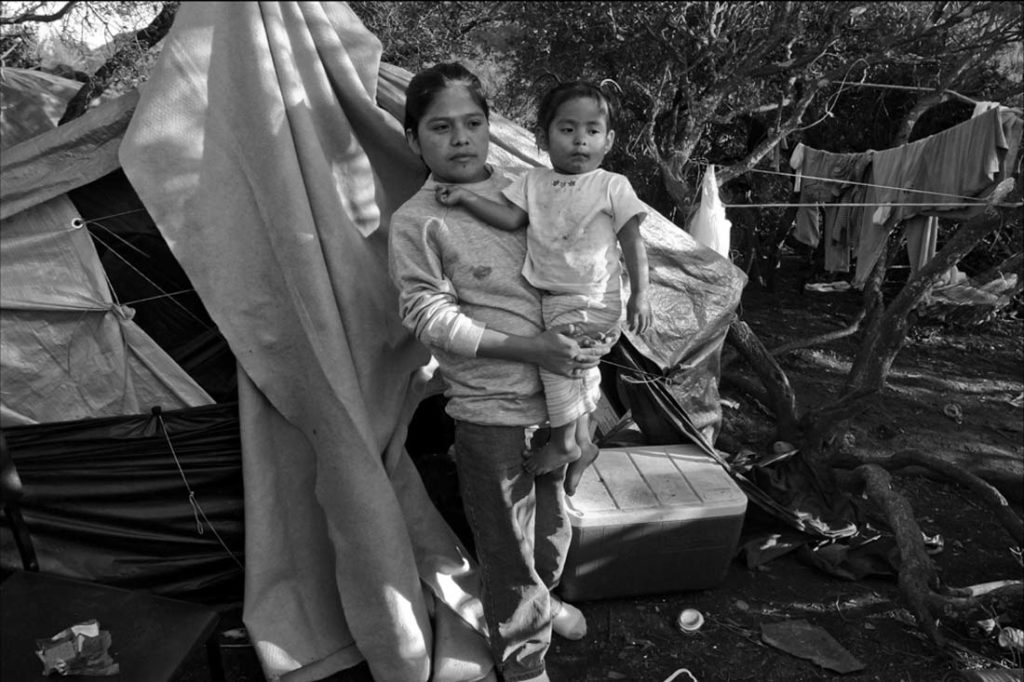 A farm worker raises her young son in a tent on a hillside in Del Mar. There is no running water for washing her child or for cooking over the camp fire. David Bacon photo