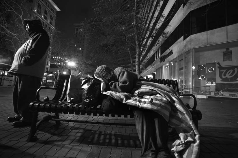 In Oakland, a homeless woman sleeps on a bus bench while a homeless man watches protectively over her. Other homeless people brought her food and blankets. David Bacon photo