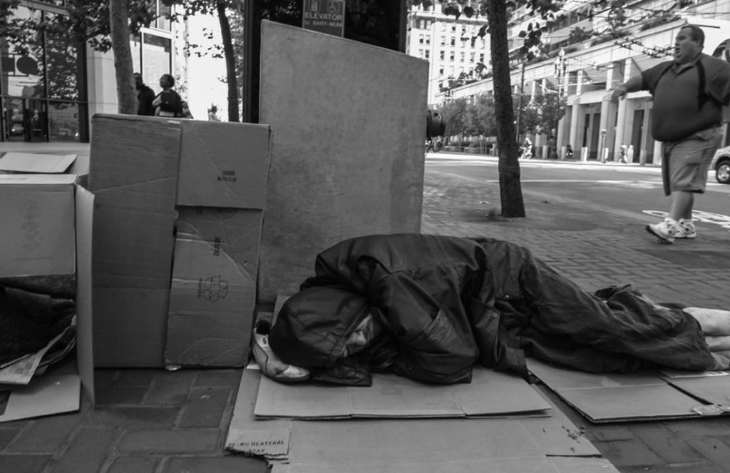 A man sleeps on a San Francisco sidewalk as passers-by pretend he's not even there. David Bacon photo
