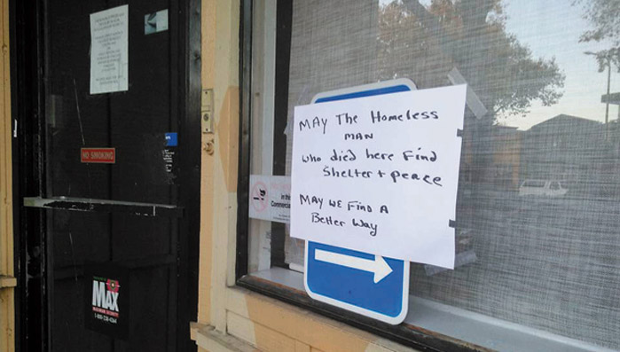 "A sign posted nearby had poignant words: ""May the homeless man who died here find shelter and peace. May we find a better way."" Daniel McMullan photo"