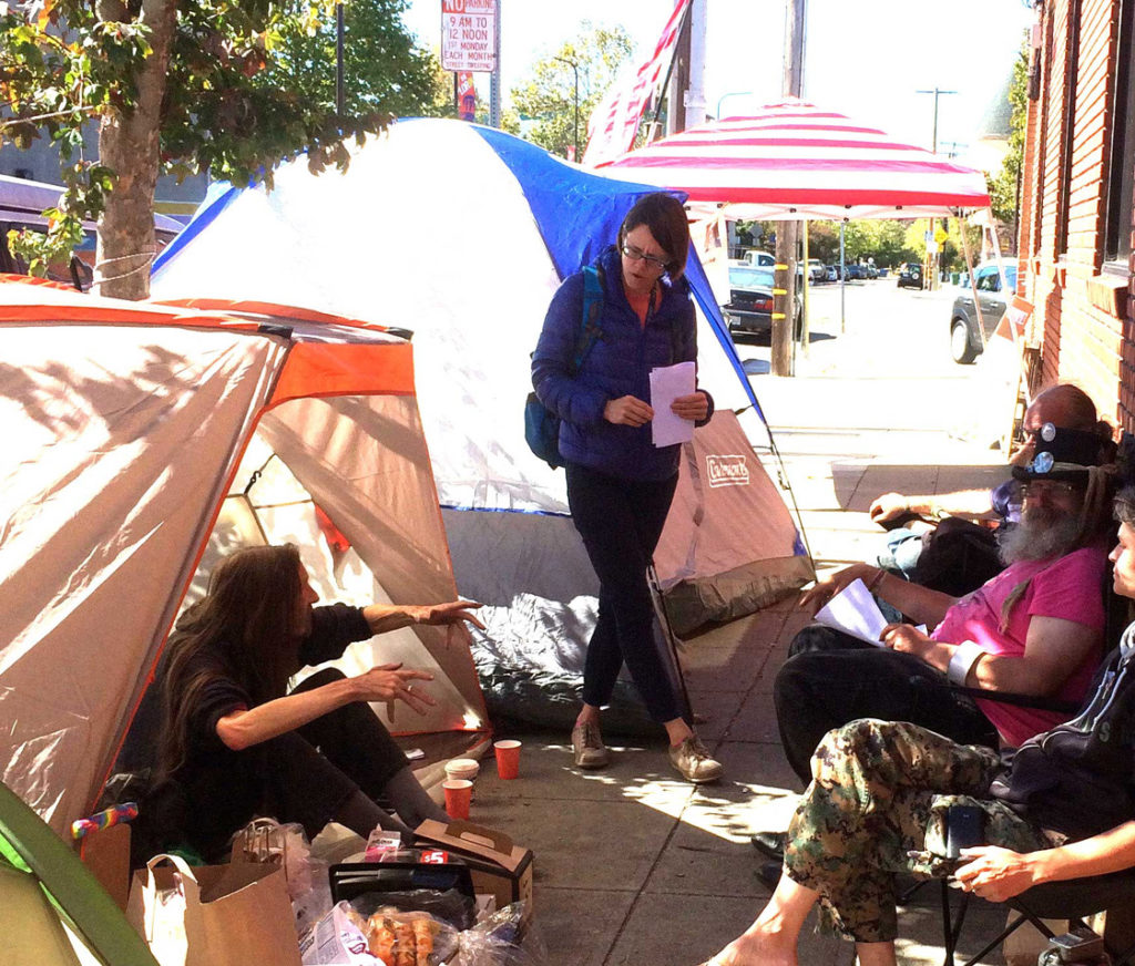 Housing activists speak to a local reporter about the little tent city they set up near the Berkeley Food and Housing Project in early October. Activist Michael Diehl (at right) is shown taking part in the demonstration. Photo by Carol Denney